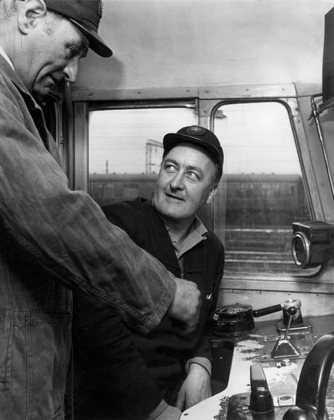 Driver Instructor CYRIL BULL, Lostock Hall, Preston, Lancashire, England (left), explains the cab layout of an electric locomotive to Preston train driver RICHARD THOMAS. Date: circa 1980