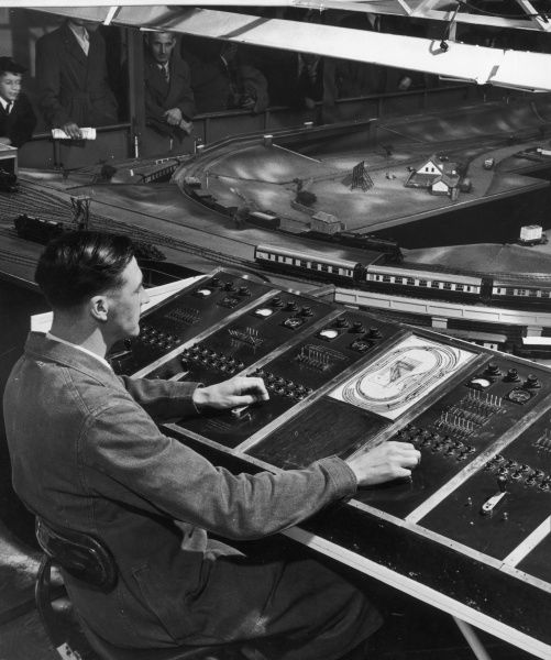 A trainee signalman operates the junctions on a model railway as part of his training. Photograph by Heinz Zinram