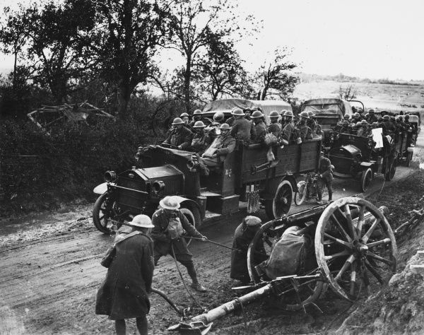 British troops on a lorry passing an 18 inch gun stuck in a ditch on the Western Front in France during World War I in October 1918