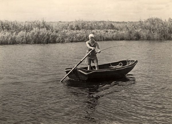A woman stands in a small rowing boat sculling and trawling for pike somewhere on the Norfolk Broads in the 1930s