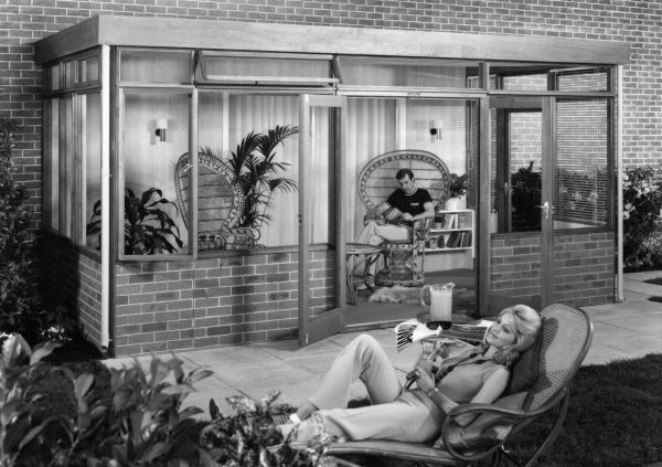 A 'trendy' new conservatory on a modern house. The man reads a book on a wicker chair in the conservatory; the woman sips a cold drink on a garden lounger chair! Date: 1960s