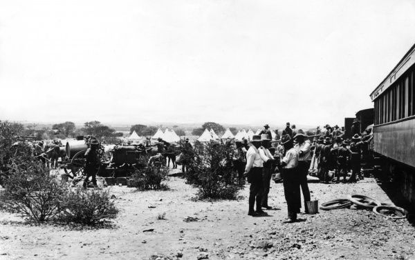 Troops at a railhead where supplies are being unloaded, somewhere in South Africa during the First World War. An encampment with tents can be seen in the background. Date: 1915