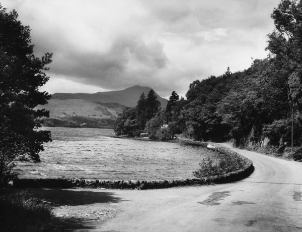 The charm of the Trossachs. The road which curls around Loch Ard, near Aberfoyle, Perthshire, Scotland, with the lofty peak of Ben Lomond in the distance