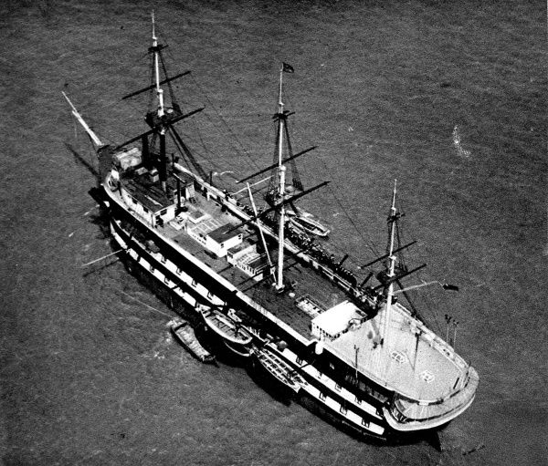 Aerial photograph showing the three-masted training ship 'Conway', moored in the River Mersey, 1935. This photograph shows the crew of boys lining the starboard bulwarks to cheer a cadet leaving the ship, after the completion of his course