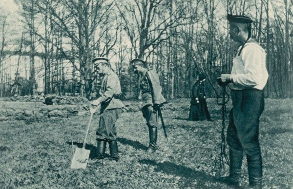 Watched by officers of the Guard, the late emperor helps to lay out a kitchen garden at Tsarskoe-selo. On the right, stands the sailor, Nagorny, who was later shot by the Bolshevists