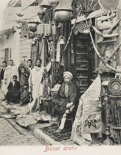 Tunisia - an Arab dealer sitting in his shop, surrounded by his wares (pretty much everything you can imagine) including drapes, rugs, pots, a stuffed baby crocodile, swords, guns, inlaid mother-of-pearl tables, plates, lamps and candlesticks