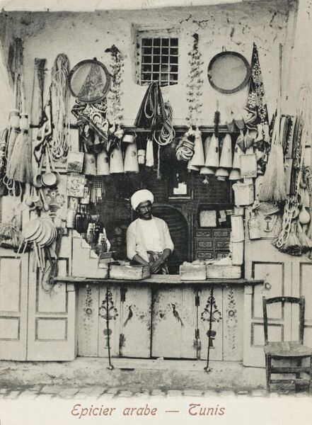 Arab Grocer in Tunis, Tunisia. Some of the items for sale include hand brushes, vegetables, candles, bottles containing drinks or potions, sieves, pans, baskets and rope