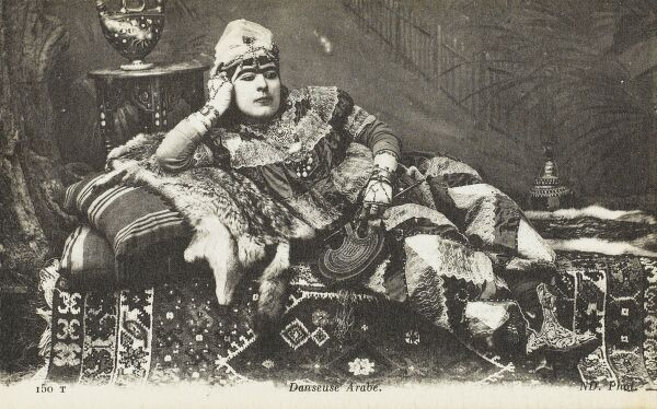 A transvestite - in the garb of an arab dancer, reclining on a fur pelt and plump cushions, adorned with vast quantities of jewellery and patterned clothing