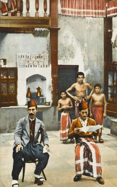 A Scene inside a Turkish bath. One gentleman reads the daily newspaper, while three serving boys stand at the rear awaiting instruction. The wooden shoes are to be worn inside the bathing complex - they are raised with a hole between sole and heel