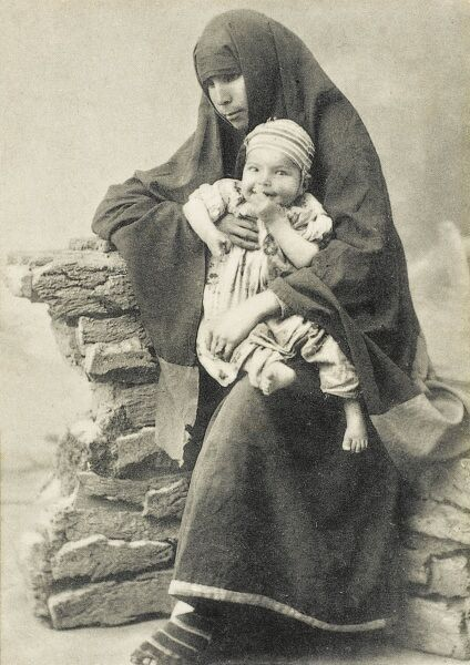 A Turkish beggar woman seated, holding her young child in very simple clothing