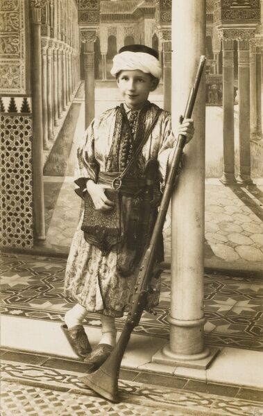Young Turkish boy standing for a portrait photograph with a traditional rifle. He also wears a loose pouch and carries a long curved knife