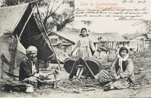 Turkish Gypsies at home. A girl operates a large set of hand bellows, whilst her father works metal on a small anvil next to their tent