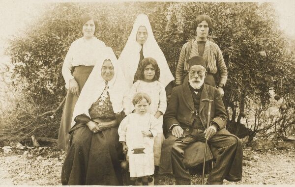 A Turkish peasant family group photograph. Situated on their farm in Central Anatolia. The seated man's two wives wear traditional headdresses as befits married women. The unmarried women are allowed to pose without any covering on their heads