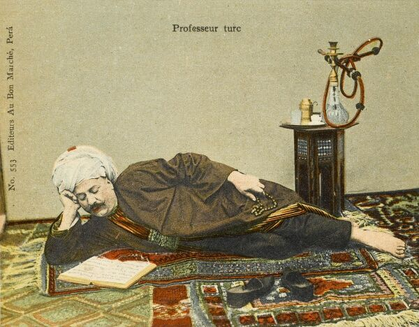 A Turkish professor, wearing a large white turban, lies down to readi a text on a fine Turkish carpet (or four!) with a Hookah Pipe on a small hexagonal Mother-of-pearl inlaid table behind him
