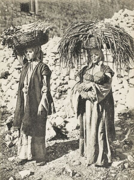 Two Turkish peasant women carrying a variety of vegetables and animal fodder in baskets balanced on their heads