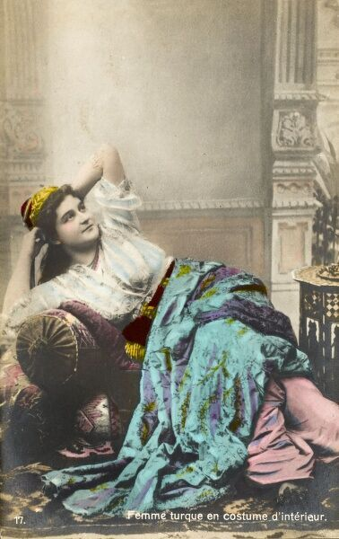 A Turkish woman in her interior house clothing, reclines on an Ottoman settee