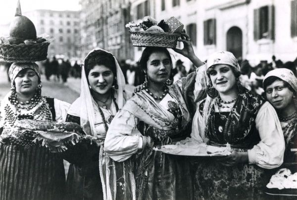 Turkish women in traditional costumes and headscarves, some of them carrying goods on their heads. Date: 1940s