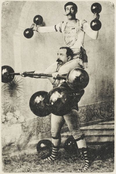 A Turkish wrestler, Ryza Bey, lifts enormous dumbells whilst another strongman colleague sits on his shoulders