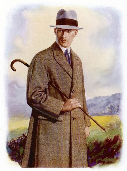 Young man sets out for walk over the moors in a single- breasted tweed overcoat with raglan sleeves & pocket flaps, he also wears a grey fedora hat with black hatband