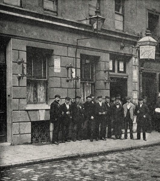 A group of men stand outside a lodging house in the East End of London