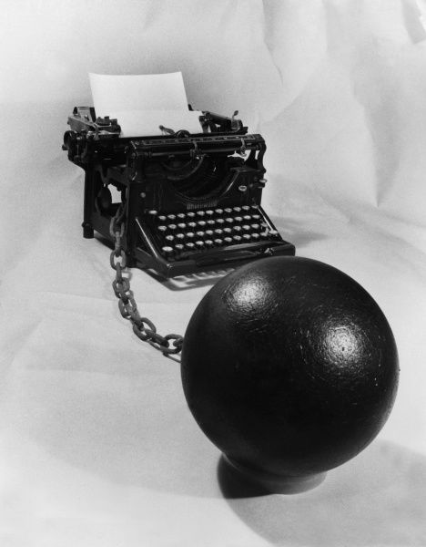 A typewriter with a ball and chain attached to it - a life sentence of office work!  1960s