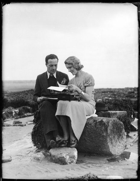 A young woman types a letter on the beach, with her boss or boyfriend beside her