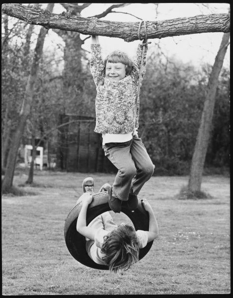 Two boys playing on a tyre swing!