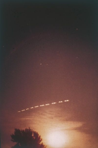 Student Michel Imbeault, 16, delivering papers at 5.30 am, sees string of 10 lights following St Lawrence river, Montreal, and takes this photo, never explained