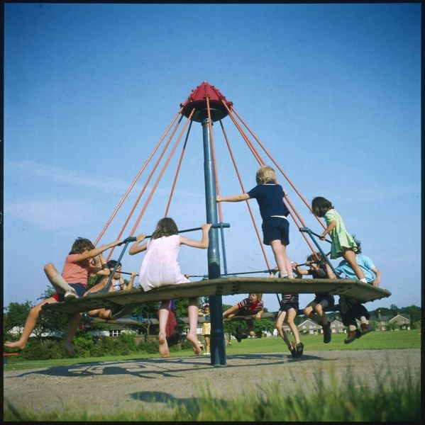 Children playing on an 'umbrella' roundabout on Lindfield Common, Sussex, England