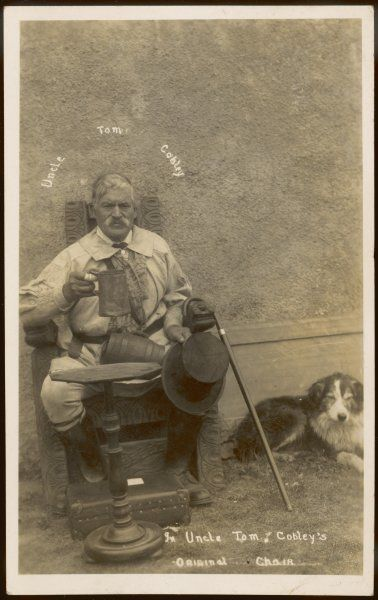 Uncle Tom Cobley sits in his chair, while his dog lies placidly beside him