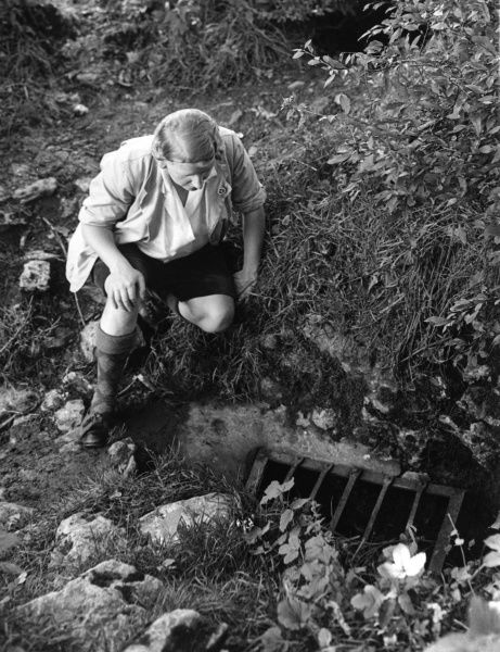 A blonde rambler wearing Argyll socks looks at a grate near Priddy, Mendips, Somerset, England. Down this cleft vanishes an underground stream to Wookey Hole caves! Date: 1930s