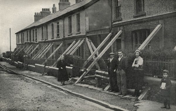 A row of houses at Blaenavon, Monmouthshire, supported by wooden props because of subsidence resulting from mining beneath them. Date: circa 1936