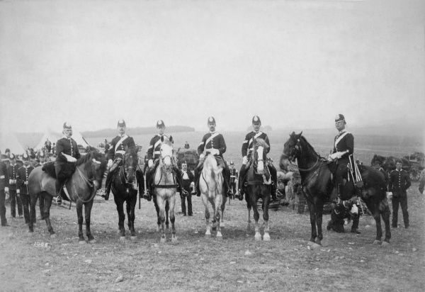 Six uniformed men (soldiers or policemen) on horseback in a field, with other men standing in the background
