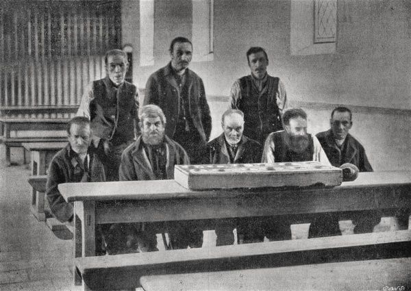 A group of male inmates at the Bailieborough Union workhouse, County Cavan, Ireland. The men are in the workhouse dining hall with their food, probably porridge, being served in a feeding trough containing a portion for each, eaten while standing