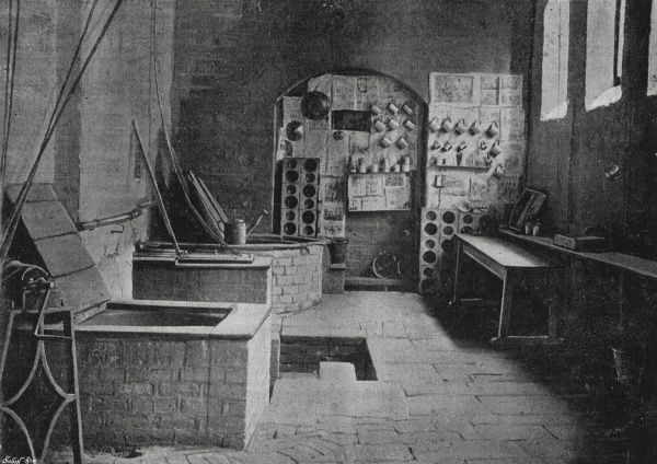 The kitchen at the Cootehill Union Workhouse, County Cavan, Ireland. A mangle and large copper stand at the left. On the far wall hang tin mugs and wooden 'troughs' in which food is served