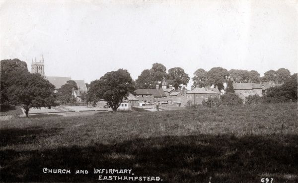 A distant view of the Easthampstead Union workhouse, Berkshire, opened in about 1836, in buildings adapted from former almshouses. The nearby church of St Mary Magdalen and St Michael appears at the left of the picture