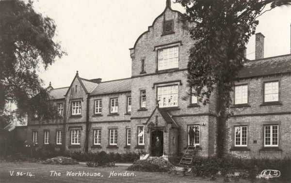 The Howden Union workhouse, erected in 1839 on Knedlington Road, Howden, East Yorkshire. A man, perhaps the master, stands on the doorstep while a workman stands on a ladder to clean windows. The site later became Howden Hospital