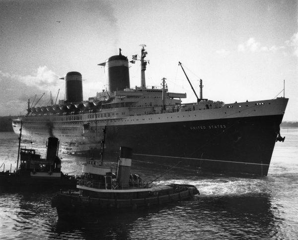An American passenger ship is helped into port by some tug boats. Date
