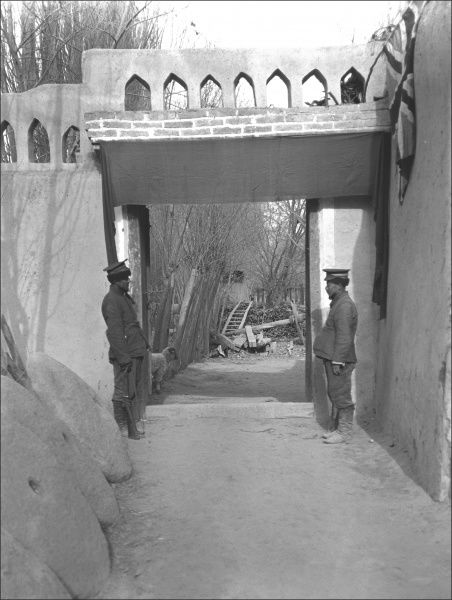 An unidentified location, somewhere in the Middle East, with two soldiers standing on guard. There is a national flag near the top of the right-hand wall. On the left are circular stones of the kind used for grinding corn