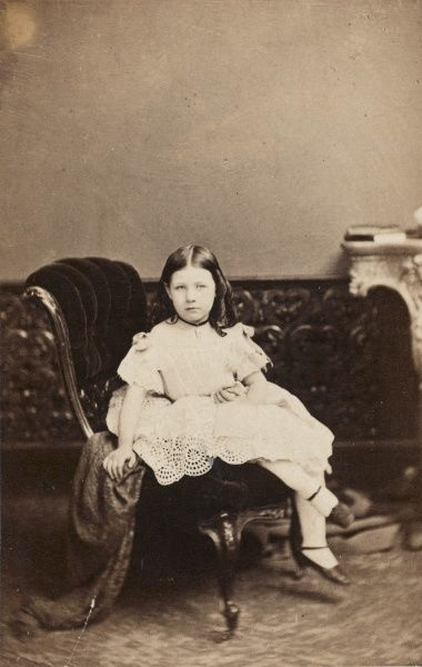An upper class Victorian girl, Alice Polhill-Turner (Alice Kate Frances, 1856-1931), seen here at the age of six, sitting on an upholstered chair in a lacy white dress and white stockings. She lived at Howbury Hall, Renhold, Bedfordshire