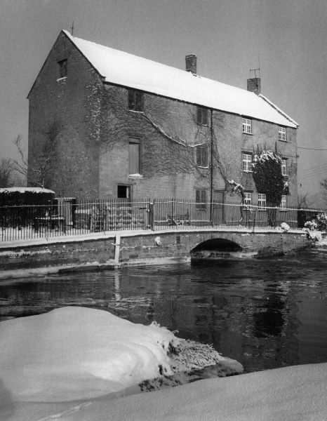 A picturesque view of Upton Mill, on the River Nene at Upton, Northamptonshire, England, after a fall of snow. Date: 1960s