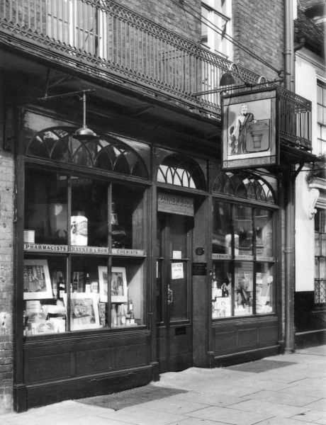The attractive shop front of Rayner & Son, Chemists, on the High Street, Uxbridge, Middlesex, England. Note the handsome shop sign of an old time apothecary. Date: 19th century