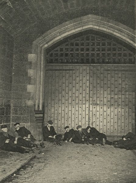 A group of vagrants sleeping rough under an archway in front of some large gates, somewhere in London