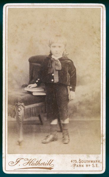 Boy wears a velvet suit of narrow cut short trousers & blouse with buttoned cuffs & square sailor collar, ribbon bow at the neck, socks & leather lace up shoes