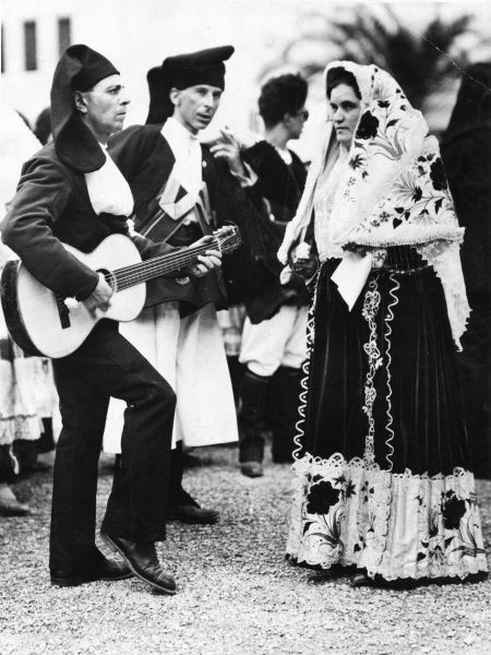 Venetian society in San Marco Square, Venice, Italy, wearing Sardinian and Neapolitan traditional costumes during the famous Venice Carnival. Date: 15 March 1930