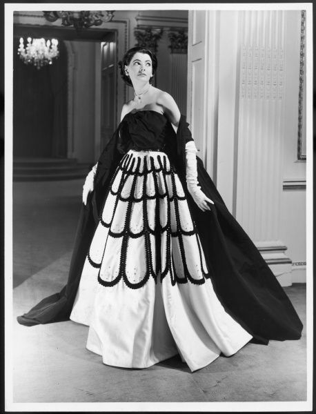 Sumptuous evening gown designed by Victor Stiebel, with bodice trimmed with a large bow, stole and sequinned full skirt