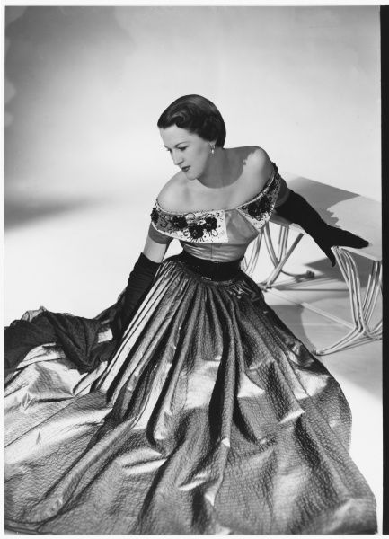 Design by Victor Stiebel for Jacqmar for a full length gown in pink slipper satin with black chiffon overskirt & scarf. Off-shoulder bodice decorated with jet
