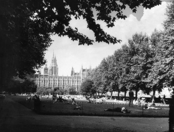 People relaxing in Victoria Tower Gardens, at the foot of Lambeth Bridge, with the the Houses of Parliament beyond, on a warm Sunday afternoon, London, England. Date: 1950s