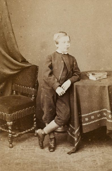 A little Victorian boy wearing jacket and breeches, leaning casually against a table in the photographer's studio