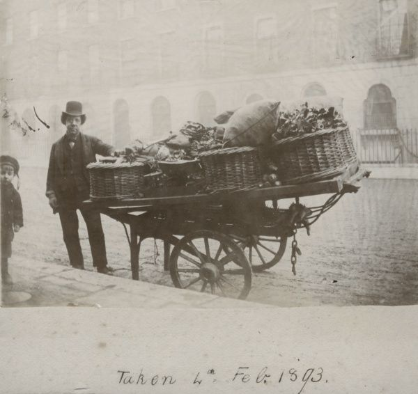 A Victorian costermonger and his cart, stacked up with baskets full of produce, photographed on a street of terraced Georgian houses. Date: 4 February 1893